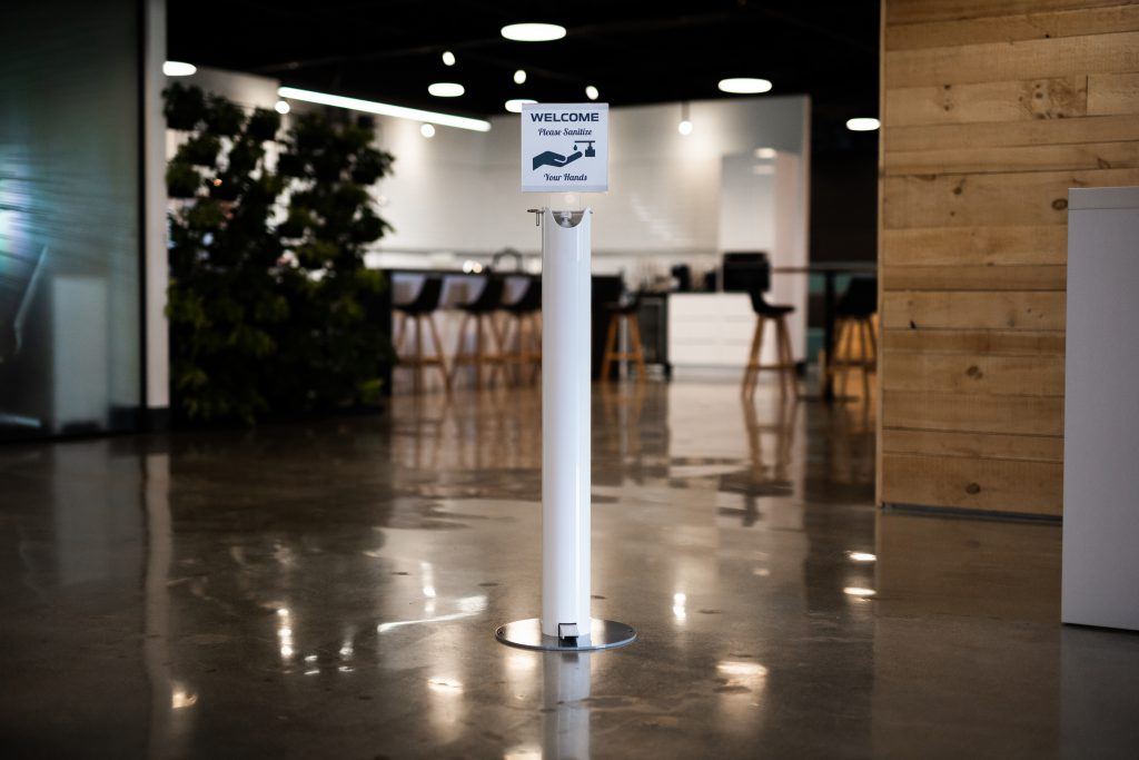 A pedal activated sanitizer stand in a reception area